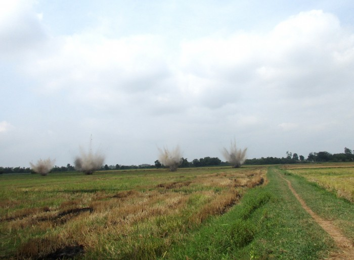 Simultaneous demolitions, as deadly cluster bombs are destroyed in place by a Project RENEW EOD team in a rice paddy in Co Luy Village.  These cluster bombs were located, identified, and marked for destruction at the same site where Team Leader Ngo Thien Khiet was killed last Wednesday.