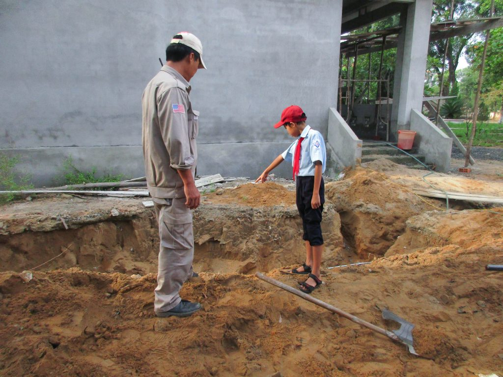 A schoolboy showing EOD Team Leader Le Xuan Tung the location where they took the soil.